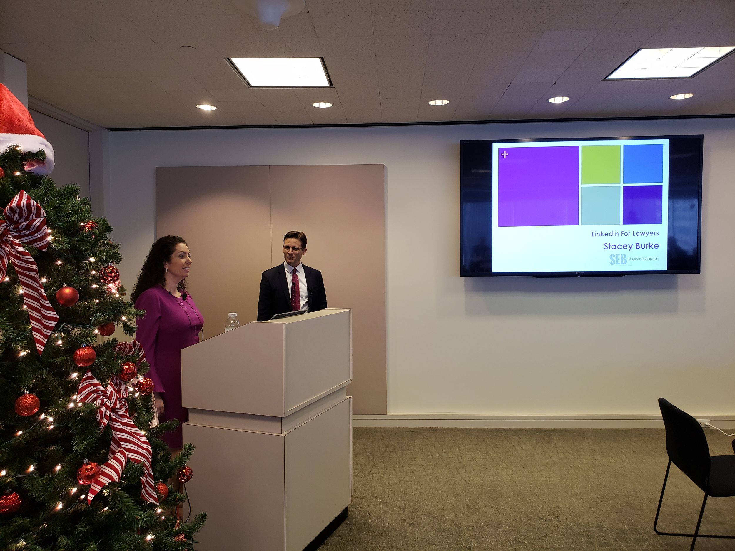 Two speakers, a man and a woman, stand at a podium in a corner, facing the viewer's right. In the foreground is a Christmas tree. Adjacent to the speakers, hanging on the wall, is a projected screen.