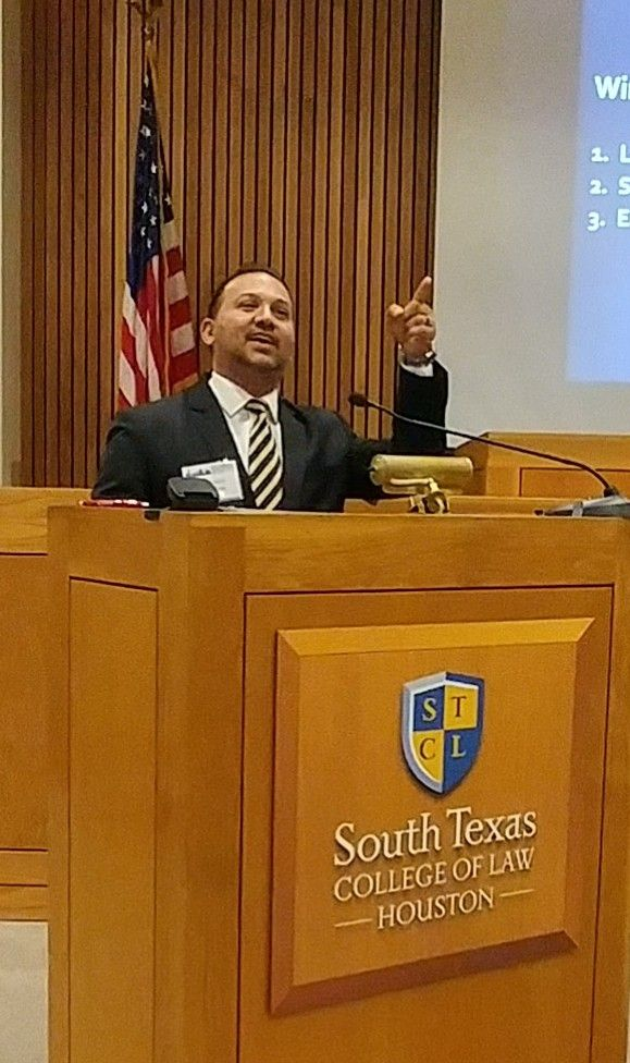 A man in a suit speaks at a podium at South Texas College of Law Houston for the ADR Section's Spring 2019 Conference.