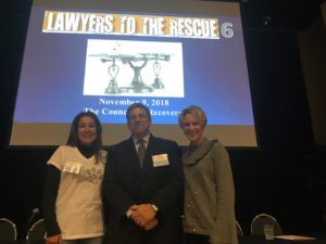 Three adults stand together in a row, facing the viewer with smiles. Behind and above them is a projected slide entitled 'Lawyers to the Rescue 6.'