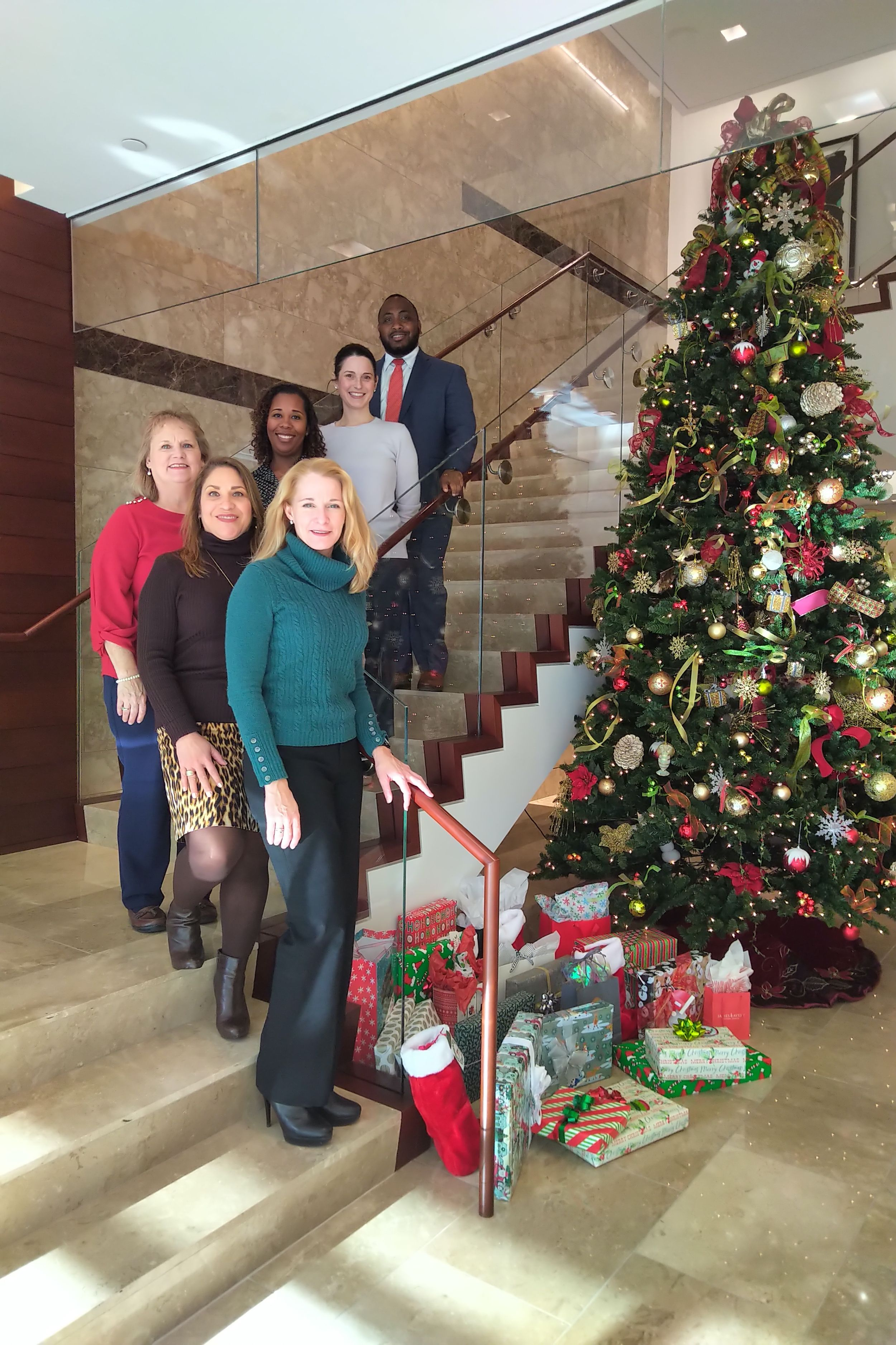 Attorneys from Baker Hostetler gather on the stairs in front of their presents.