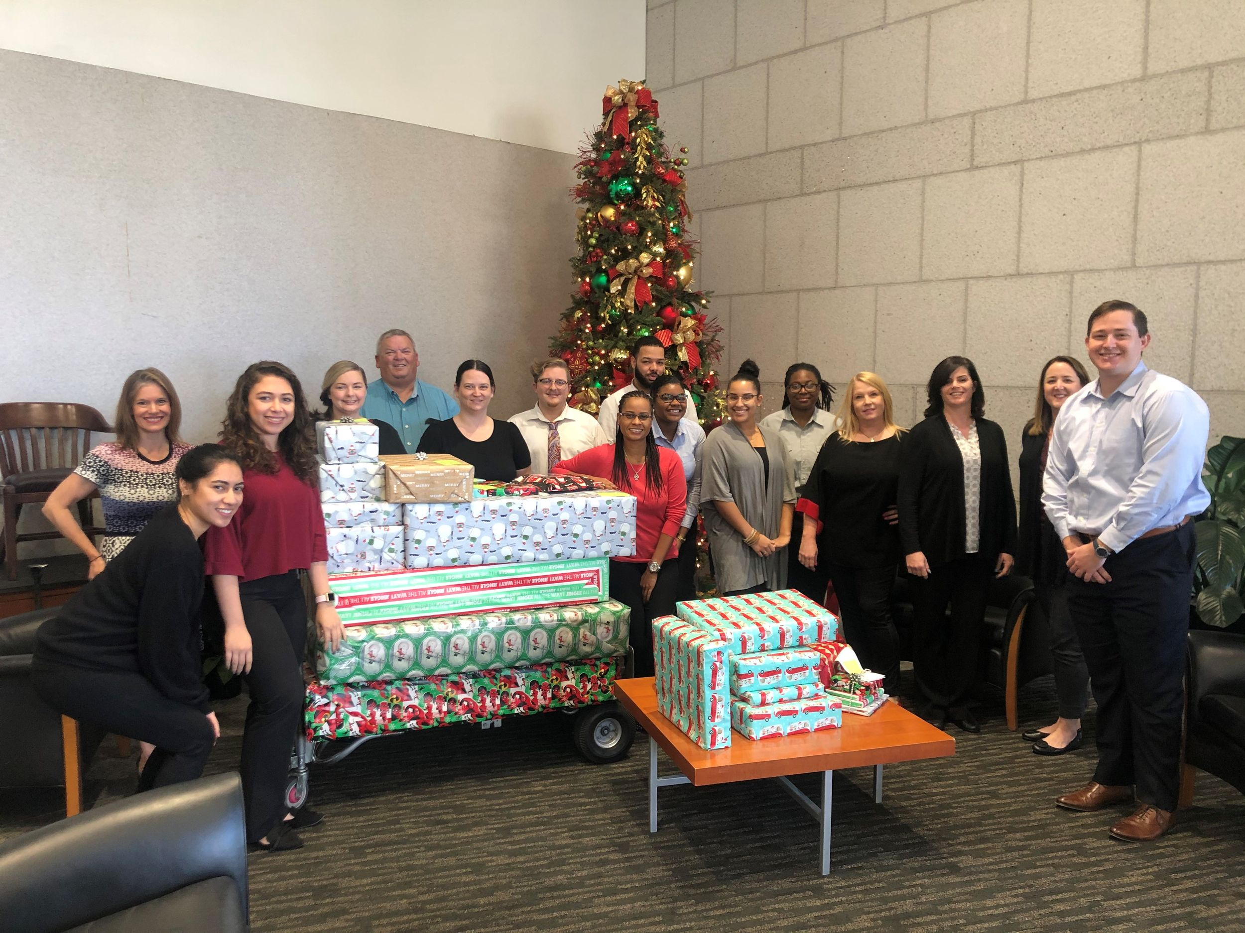 Attorneys from Brown Sims stand around their presents and Christmas tree.