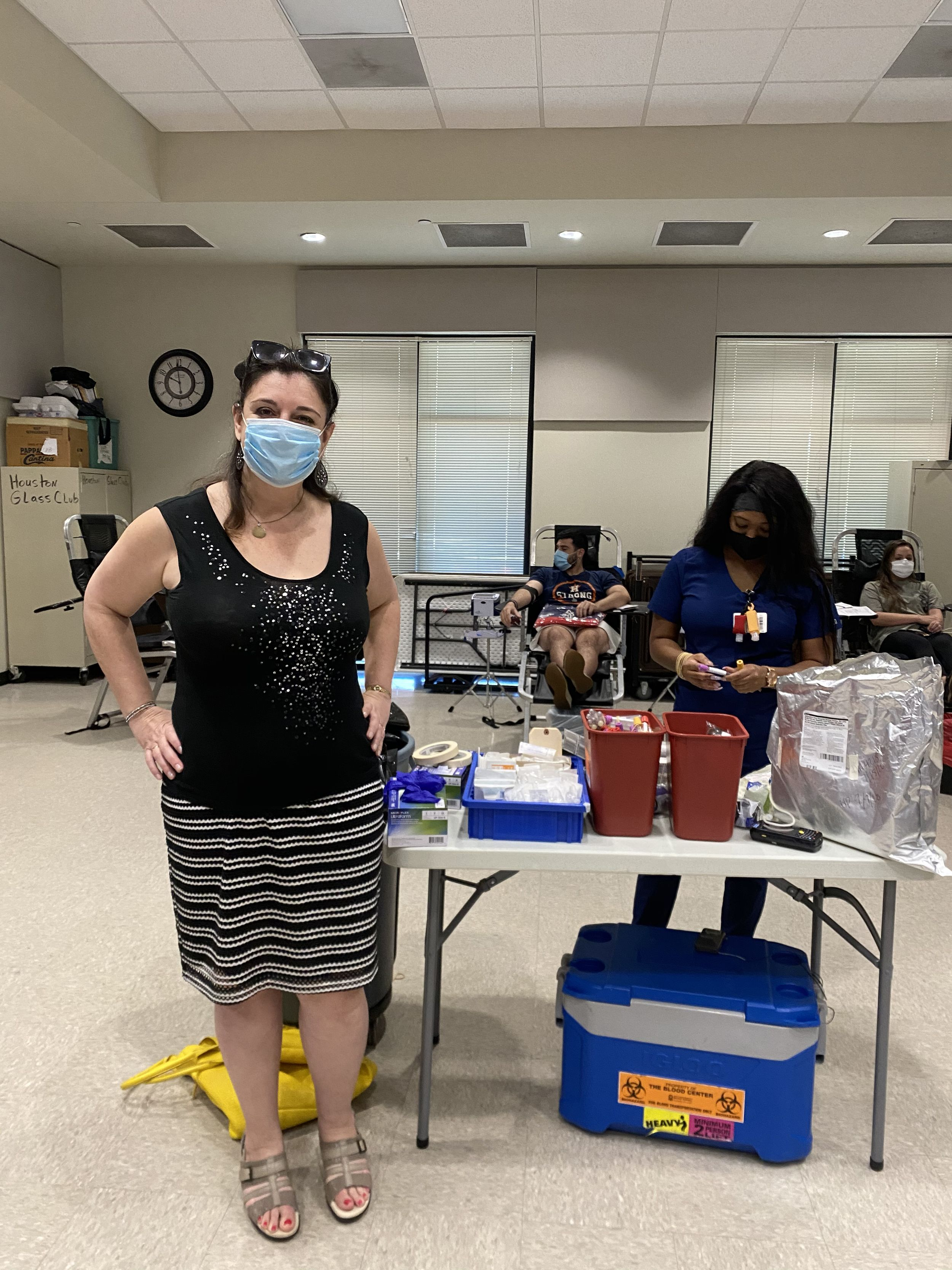 A woman in a mask stands next to a table of blood donation supplies