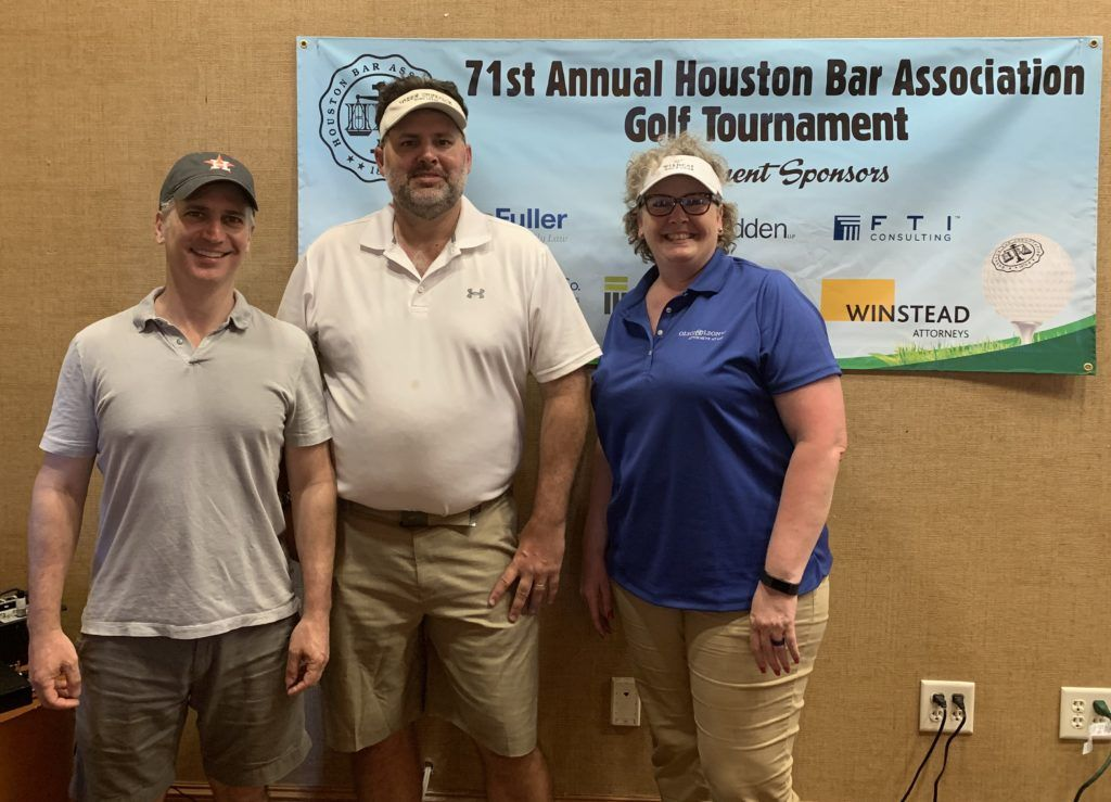 A photo of the three planning committee co-chairs, Jeff Golub, Michael Rose and Donna Johnson, smiling at the viewer and standing beside a banner advertising the 2019 tournament sponsors.