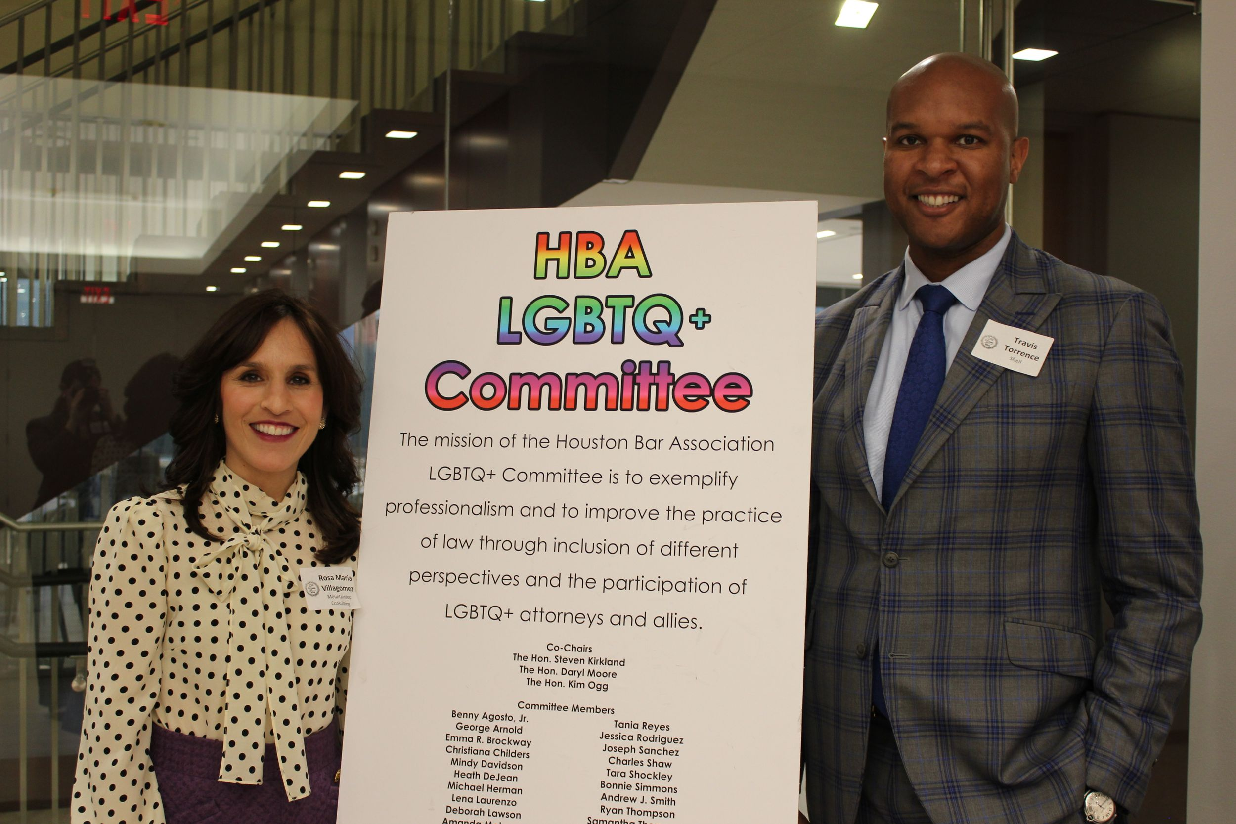 A man and a woman flank a sign for the LGBTQ Committee