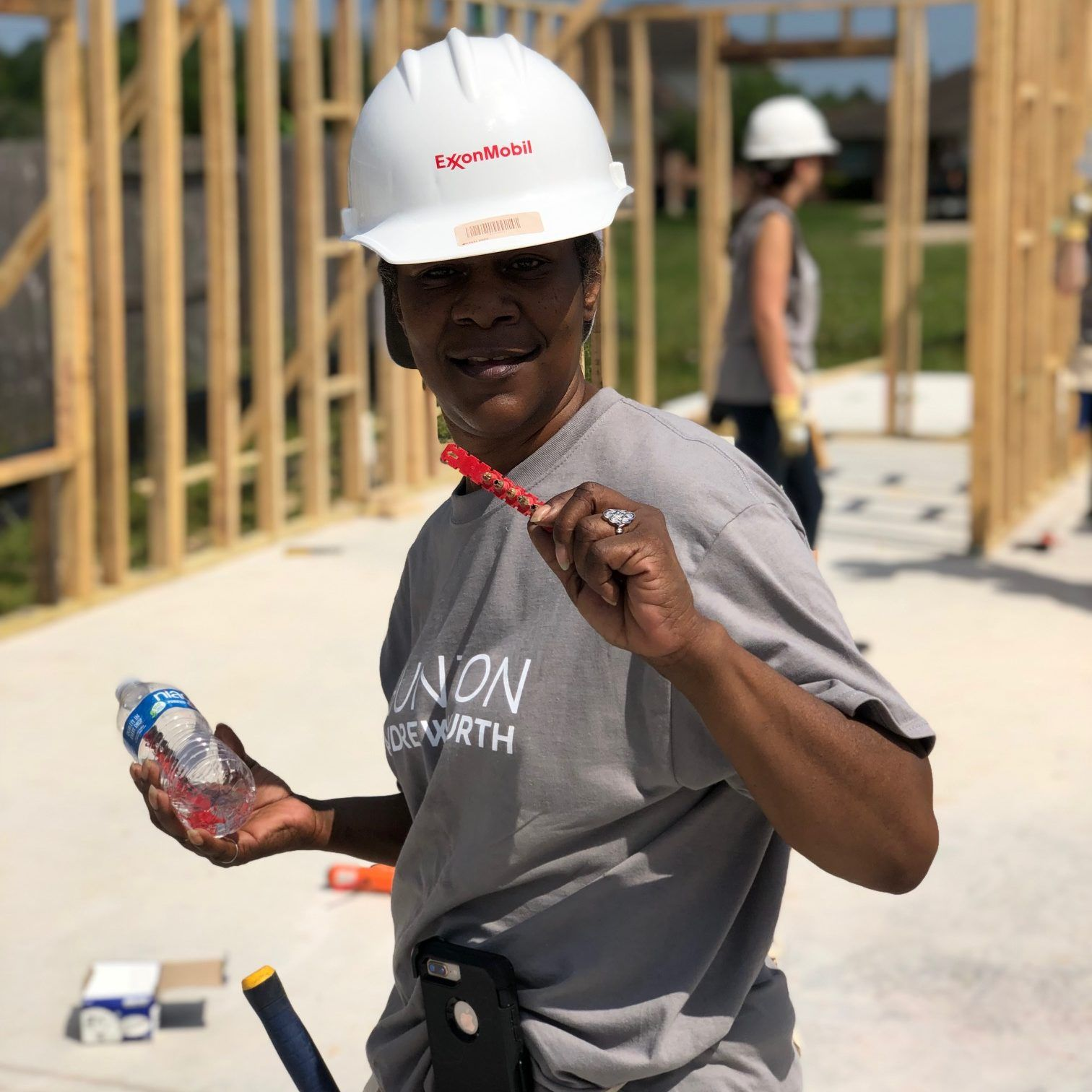 A volunteer from Hunton Andrews Kurth LLP poses in front of the build site for the HBAs 22nd Habitat for Humanity home.
