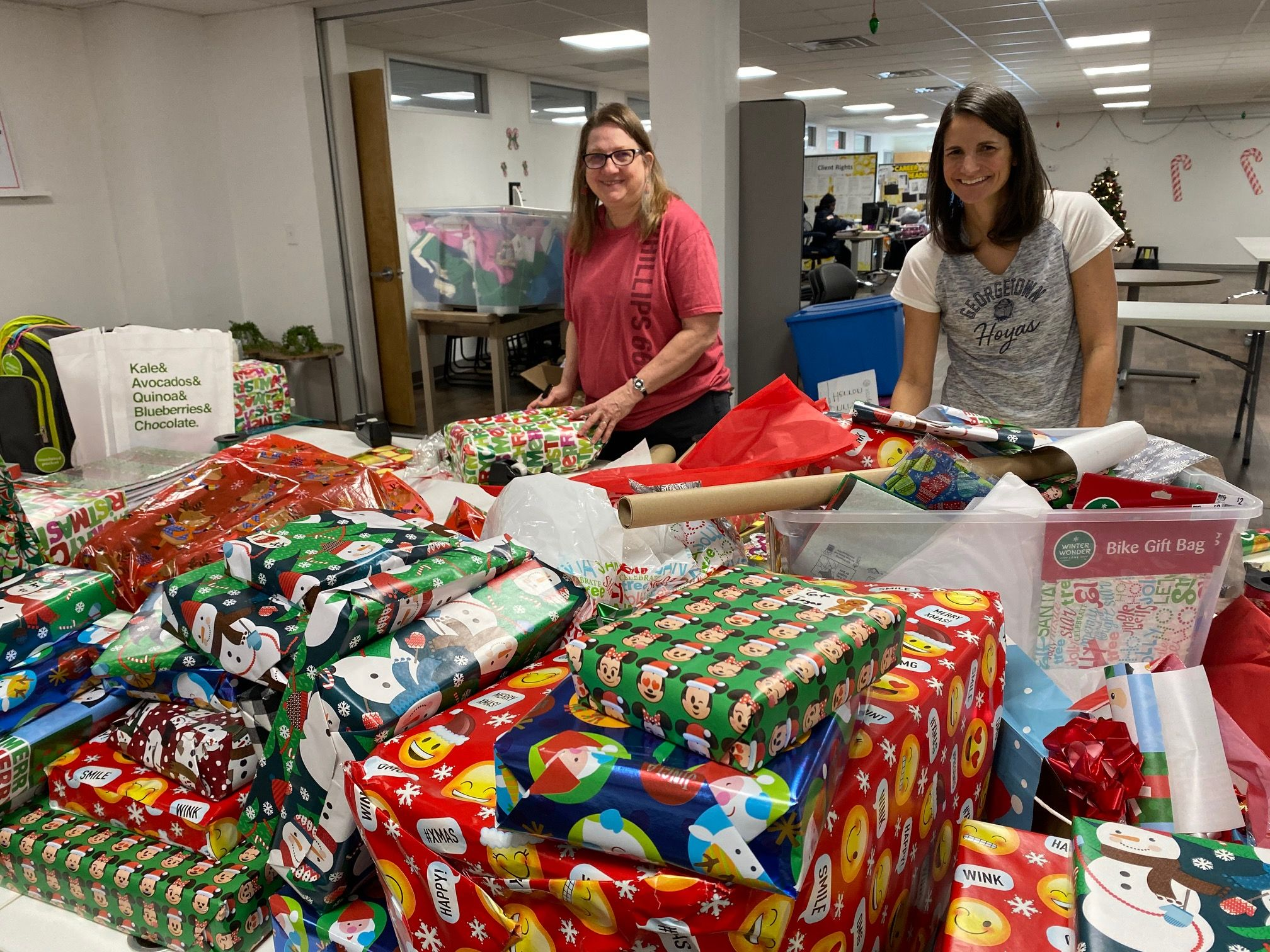 Two volunteers show a table full of wrapped presents