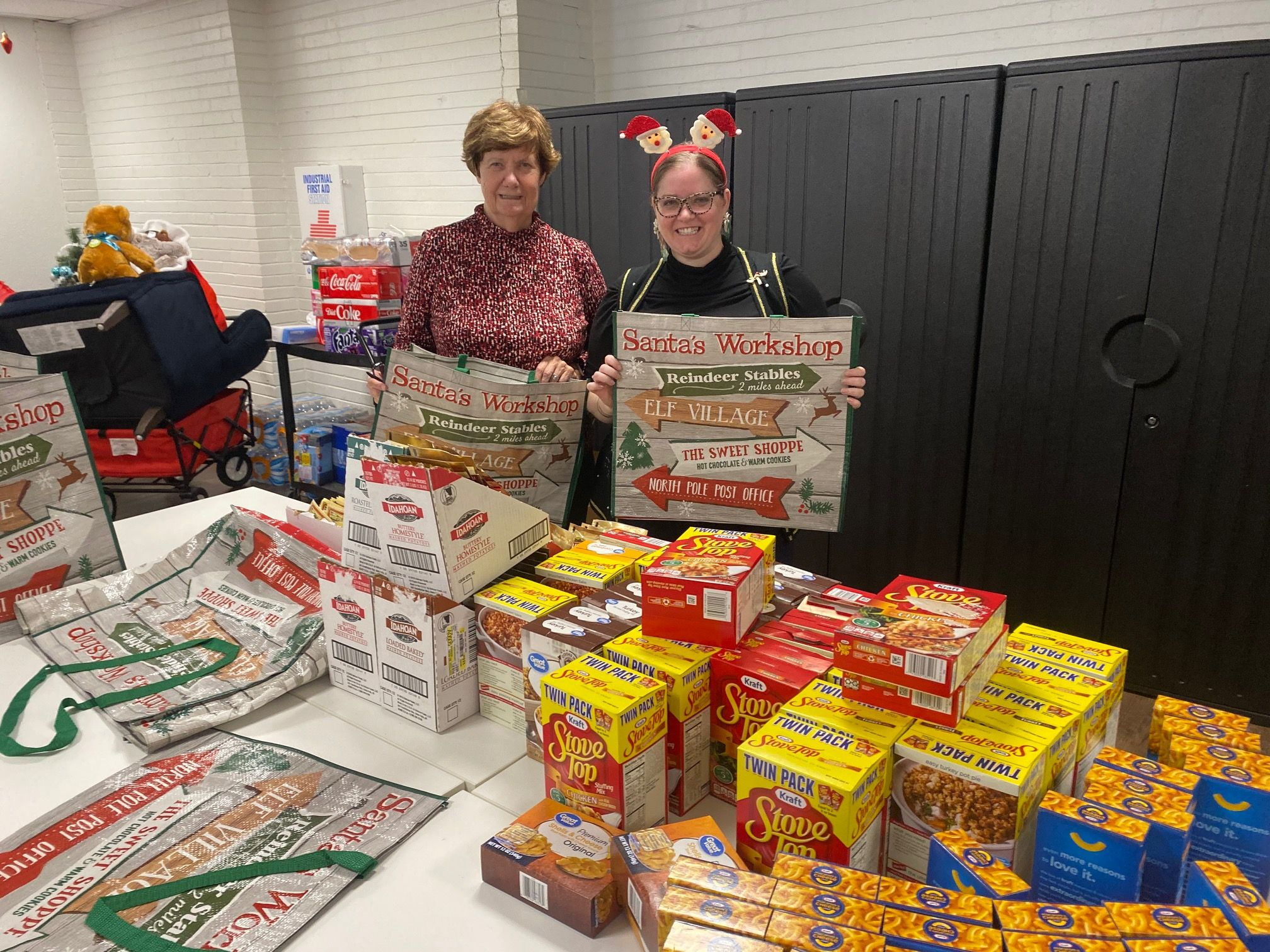 Two volunteers stand behind several boxes of food