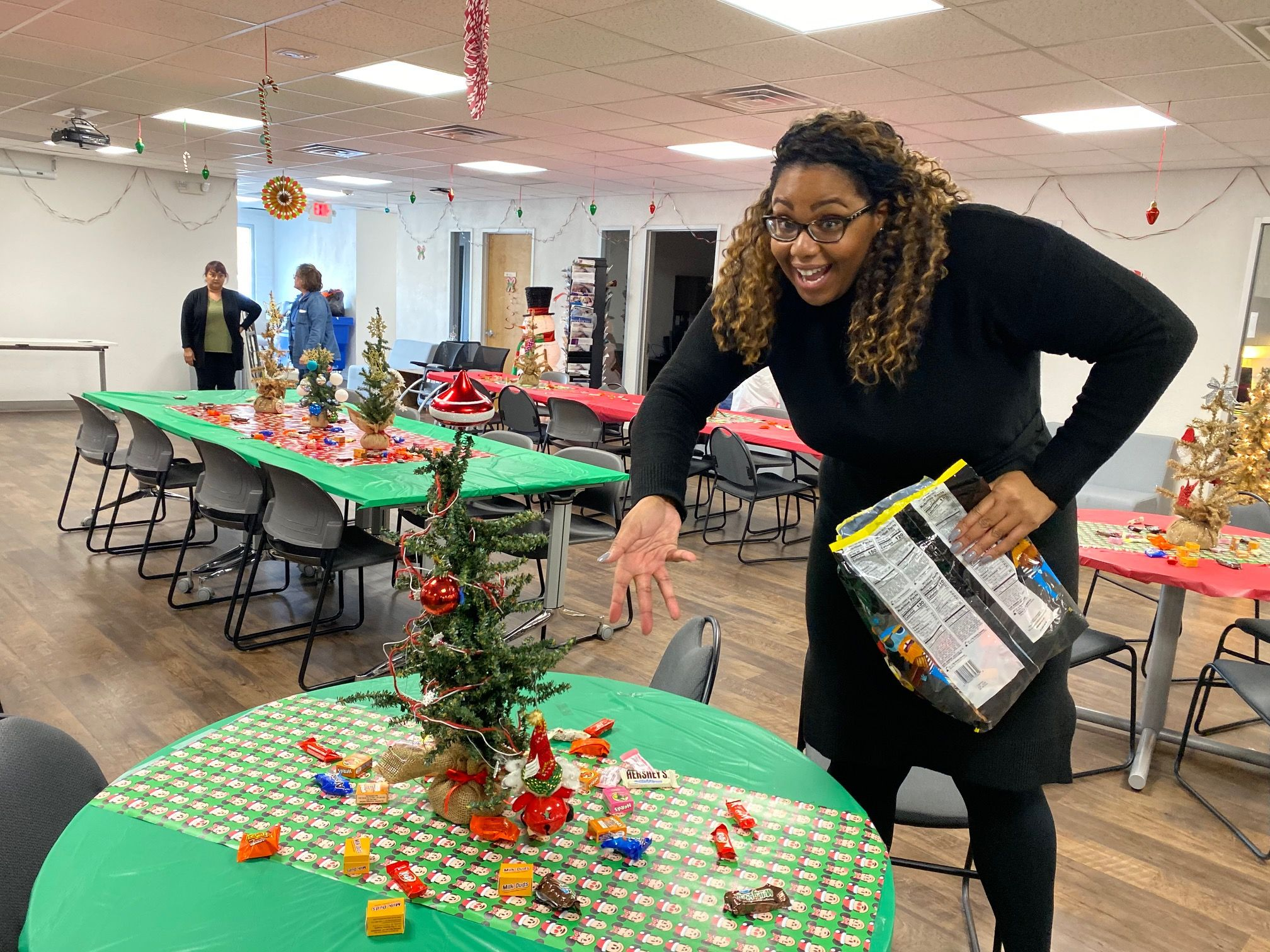 A volunteer smiles while pointing at a miniature Christmas tree