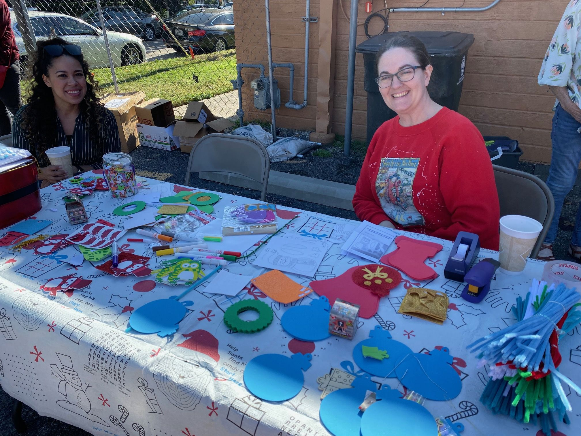 Two volunteers sit at a craft table