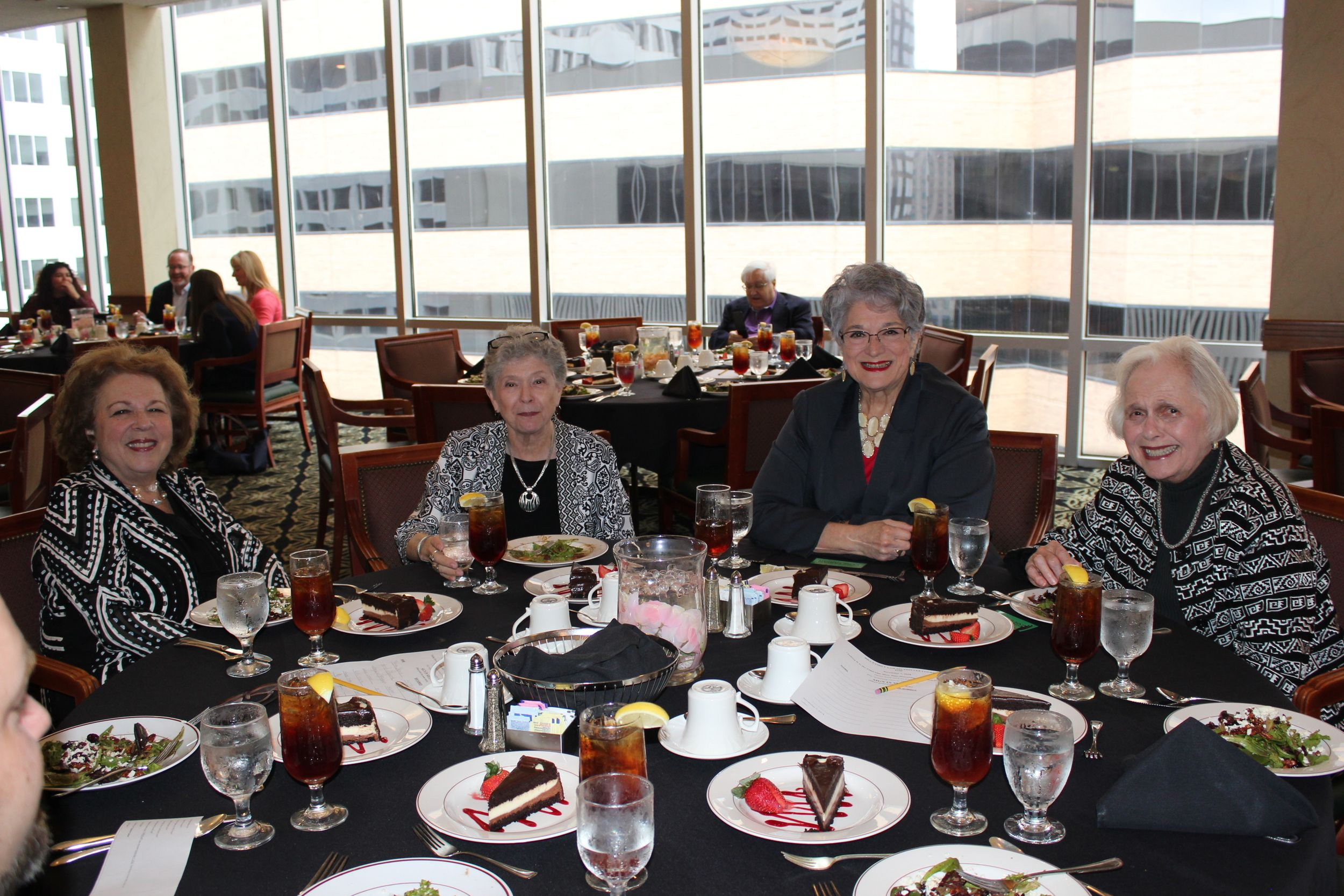 Four middle-aged women in professional attire sit at the far end of a circular table, smiling at the camera. There is food in front of them and a large window behind them.