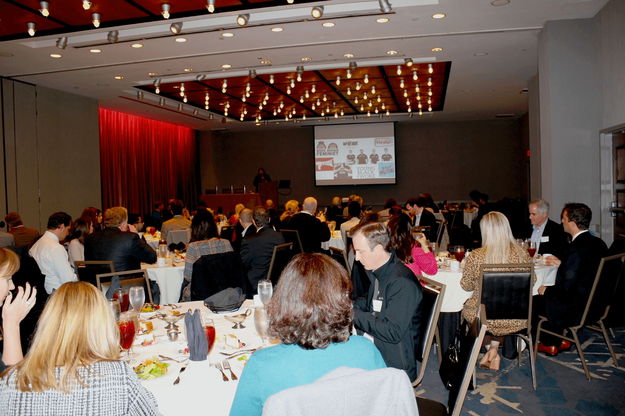 A room full of professionally-dressed adults sit at round tables and face the front, away from the viewer. They are watching a woman at a podium speak with a PowerPoint slide projected beside her.