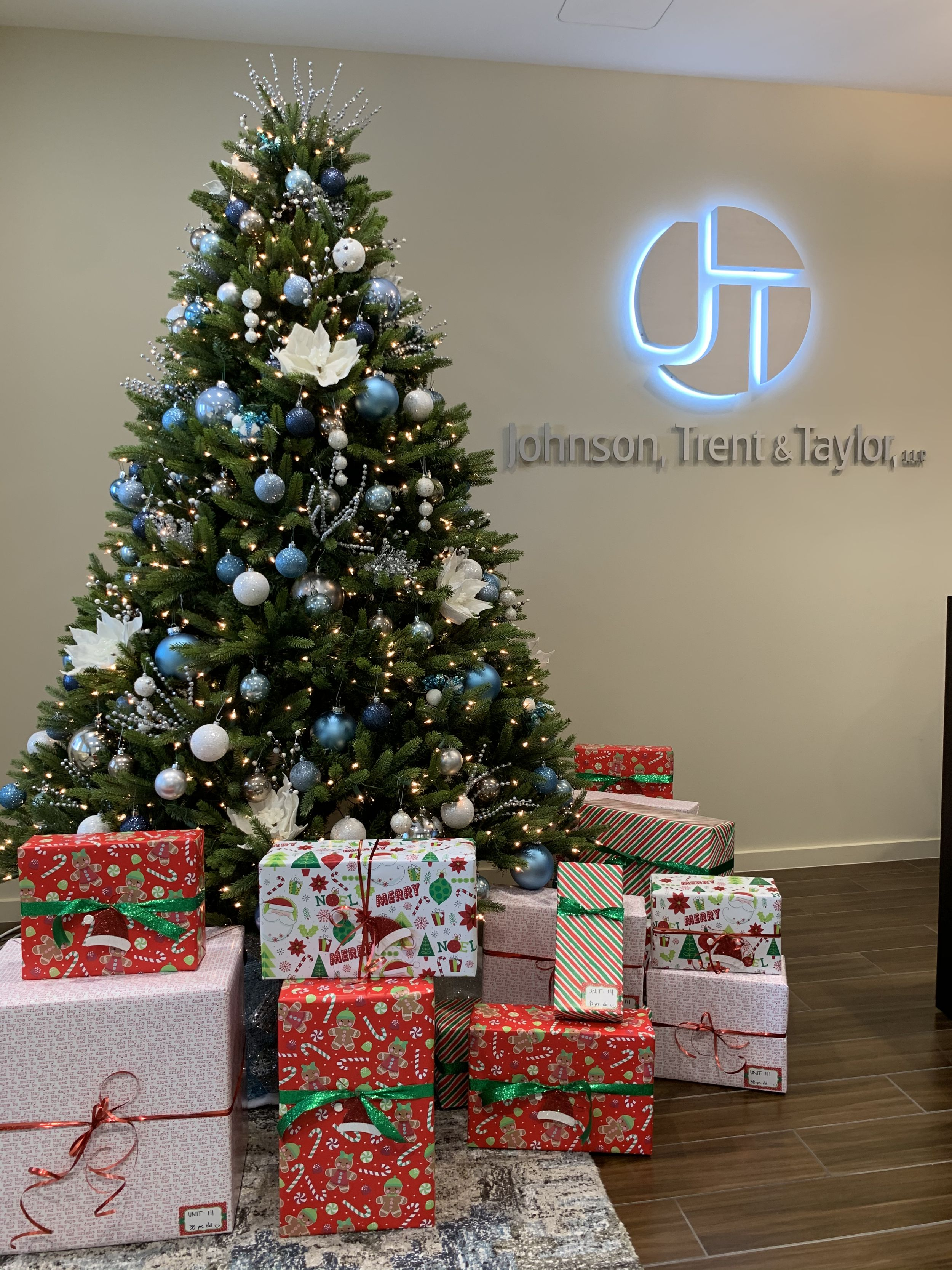 Attorneys from Johnson Trent and Taylor gather around a Christmas tree with their gifts.
