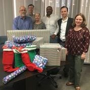 Attorneys from Ajamie LLP posing with their Adopt-a-Family gifts