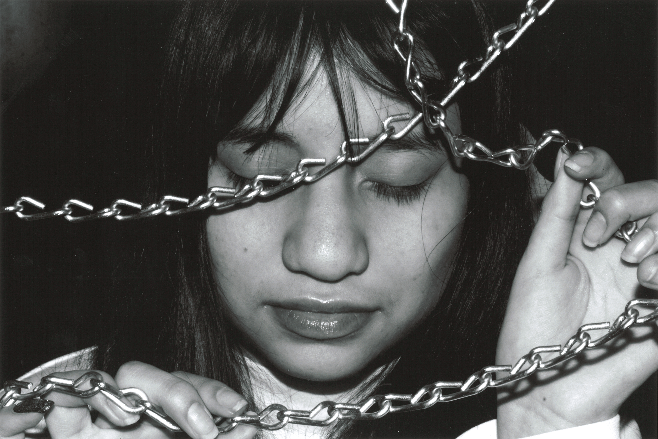 Close-up on a young woman's face framed by linked chains