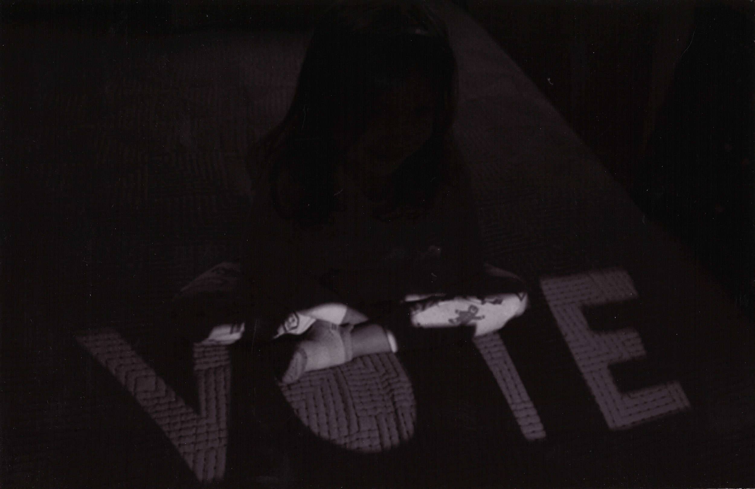 A girl sits in shadow with the word vote illuminated in front of her