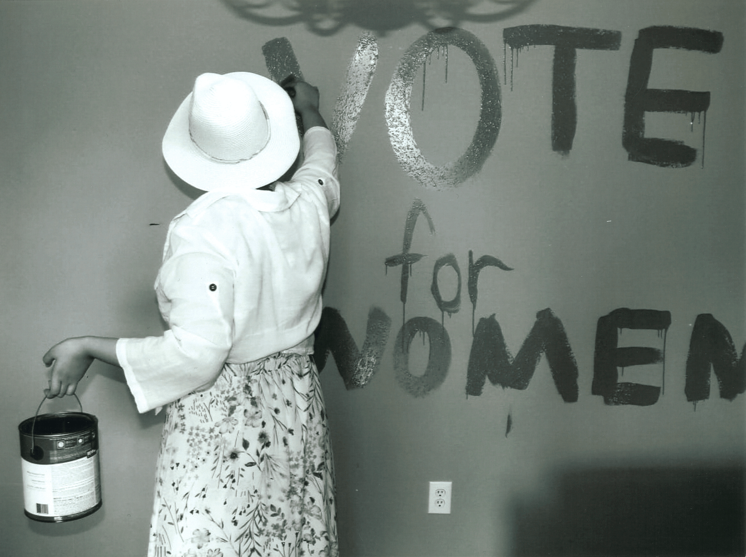 View of a woman from the back as she paints vote for women on a wall