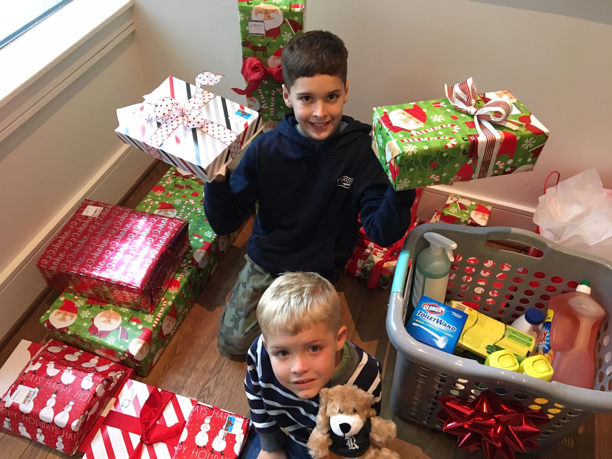 Two children sit on the floor among several wrapped presents.