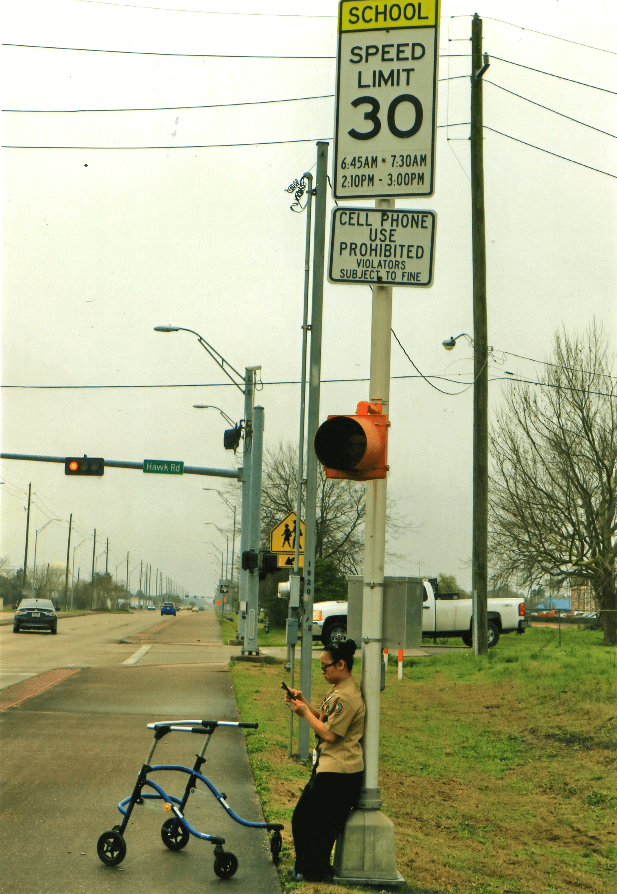 A youth stands by a school zone sign while using their cell phone